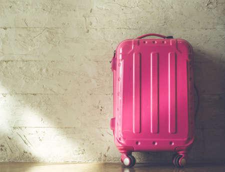 レンガの壁の背景にピンクのスーツケース 写真素材