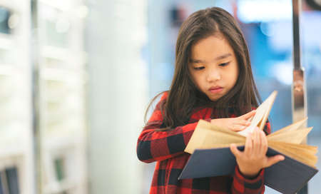 Portrait Asian child holding open textbook in hands in book store