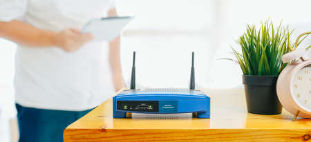closeup of a wireless router and a man using smartphone on living room at home ofiice 版權商用圖片 - 120611088