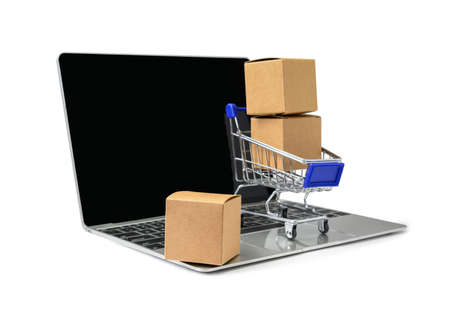 Boxes in a trolley on a laptop keyboard on white  background  . Concepts about online shopping