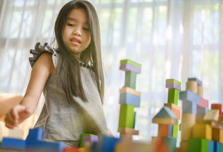 little girl in a colorful shirt playing with construction toy blocks building a tower . Kids playing. Children at day care. Child and toys. Фото со стока - 120611151