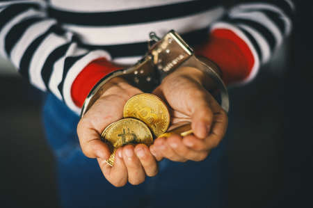 hand holding golden Bitcoin. Criminal man with handcuffs  after committed a crime