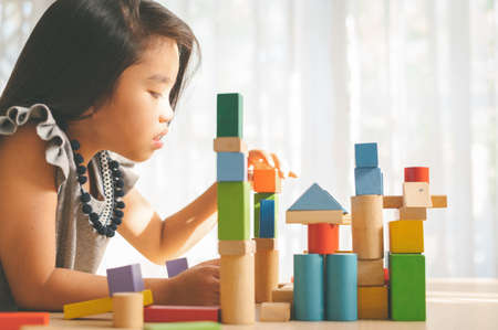 little girl in a colorful shirt playing with construction toy blocks building a tower . Kids playing. Children at day care. Child and toys. Imagens - 120611162