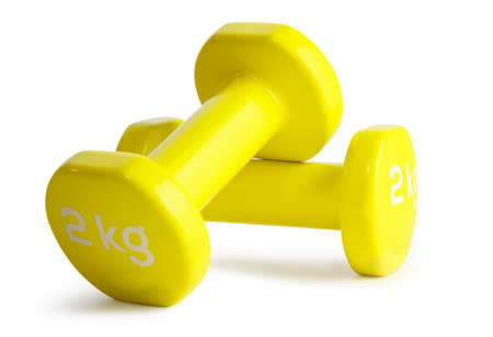 Two yellow  dumbbells isolated on white background