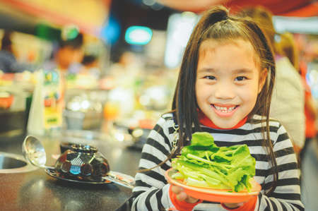 Little girl eating vegetable - healthy food concept Imagens - 122401038