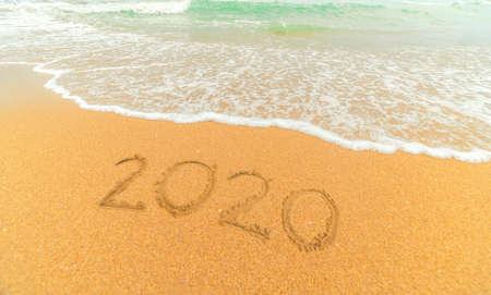 Happy New Year 2020 written on seashore sand at sunrise concept.beautiful sandy beach and soft blue ocean wave