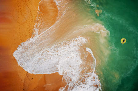 Aerial view of  woman swimming on the yellow swim ring in the  turquoise sea. Beach on aerial drone top view with ocean waves reaching shore. Top view from drone Imagens