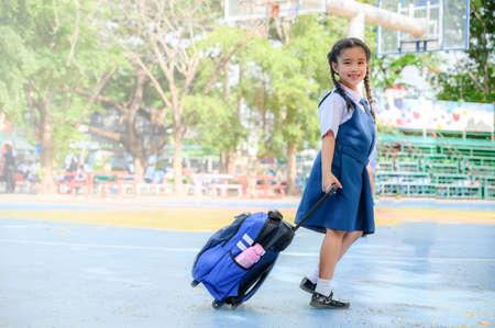back to school. Portrait of smiling Asian school girl in school uniformat the school yard.