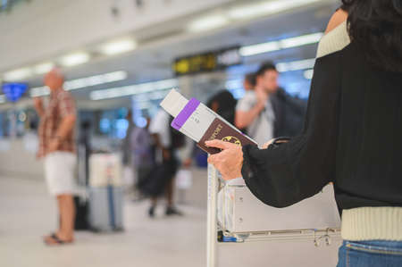Closeup of girl holding passports and boarding pass at airport 版權商用圖片 - 125019952