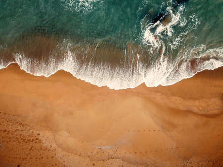 Beach on aerial drone top view with ocean waves reaching shore. Imagens