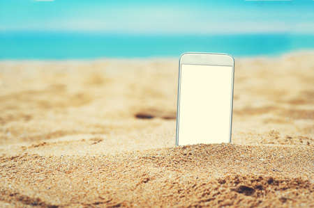smartphone in the sand on a beach in the summer Stock Photo