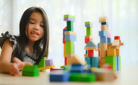 little girl in a colorful shirt playing with construction toy blocks building a tower. Kids playing. Children at day care. Child and toys. 版權商用圖片 - 129271034