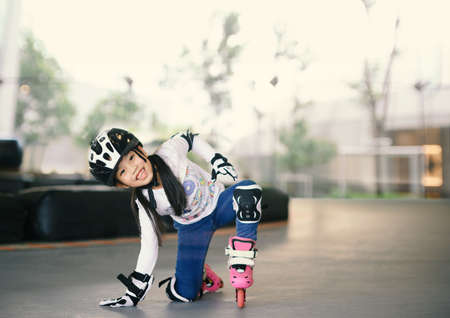 Happy Asian girl learning to roller skate. Children wearing protection pads for safe ride. Active outdoor sport for kids. 版權商用圖片