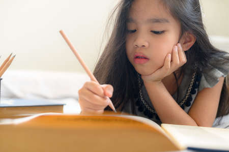 Asian girl writing with pencil and notebook