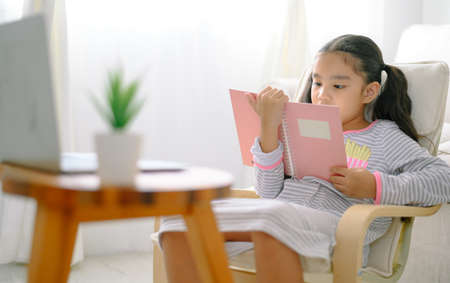 happy child little asian girl  reading a books on the table in the living room at home. family activity concept