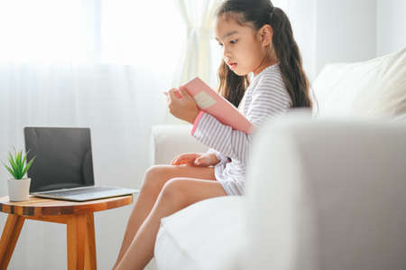 happy child little asian girl  reading a books on the table in the living room at home. family activity concept 版權商用圖片 - 129271055