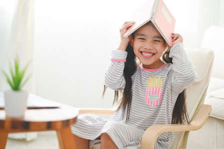 Happy little schoolgirl with book on her head. Back to school concept.