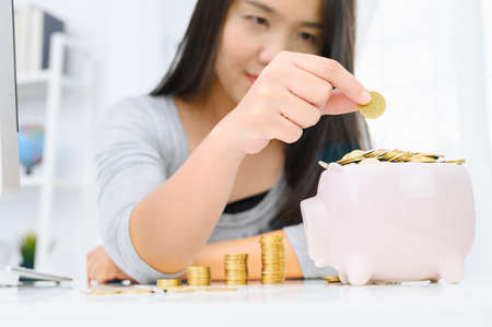 Woman putting golden coin in pink piggy bank. saving money, budget, investment, finance concept