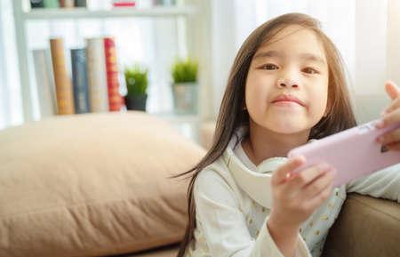 Cute little girl using smart phone at home 版權商用圖片 - 129271416