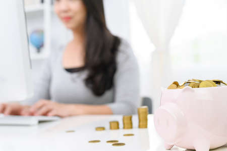 Cute piggy bank with gold coin and blur  Woman working on computer  at  home office background. concept saving money for finance accounting 版權商用圖片 - 129271428