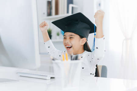 Little Asian girl wearing graduate hat doing homework and smile with happiness for success of education concept