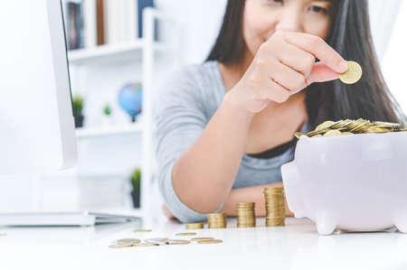 Woman putting golden coin in pink piggy bank. saving money, budget, investment, finance concept
