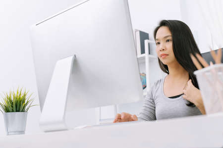 asian housewife working on computer at her home office working desk.