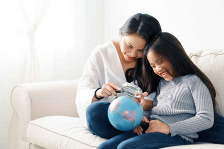 family, children, education, school and happy people concept - mother and daughter with Discovery World Learning Analysing Cartography Concept 版權商用圖片