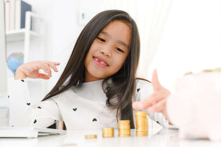 asian little girl playing with coins making stacks of money, kid saving money for the future concept 版權商用圖片