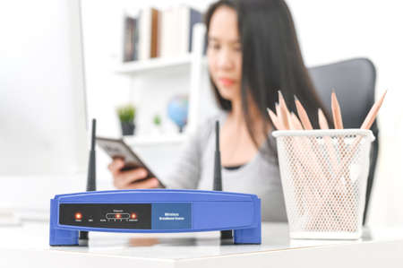 Wireless router and woman using a smartphone  in office. router wireless broadband home laptop computer phone wifi concept