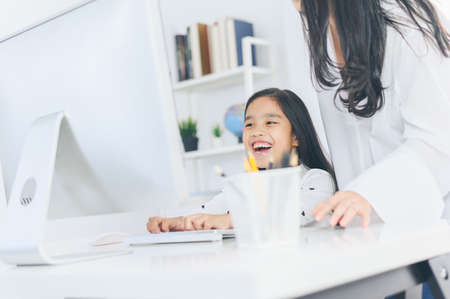 happy Little girl looking at computer with her mother 版權商用圖片