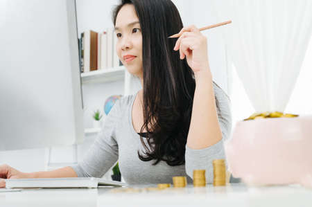 housewife having confused problem about family save and sitting in living room desk record spending thinking debt for family 版權商用圖片
