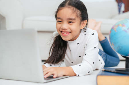 Happy Asian girl using laptop computer, concept for kids art and home school. Stock Photo