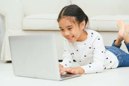 Happy Asian girl using laptop computer, concept for kid's art and home school. Banco de Imagens