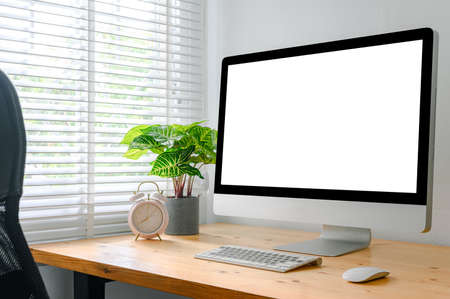 workspace with computer with blank white screen, and office supplies on a wooden desk 版權商用圖片