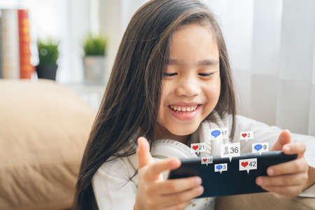 Cute child using a smartphone and smiling while sitting on sofa at home