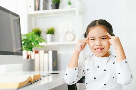 Asian girl getting headache from doing homework