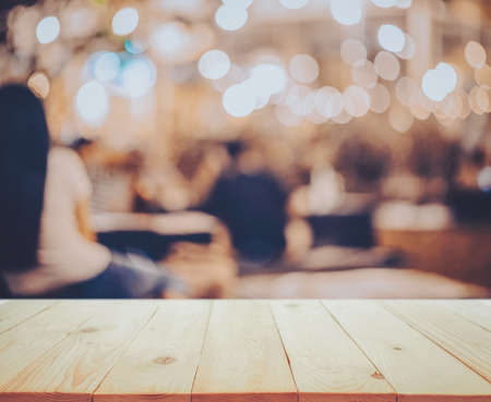 wooden table in front of abstract blurred restaurant lights background