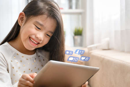 Asian  Cute child playing games with a tablet and smiling while sitting on sofa at home Stock Photo