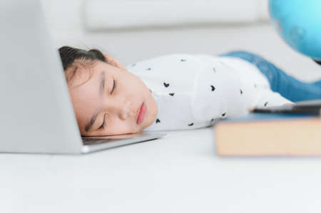 Asian primary student lying on the floor with Laptop