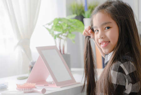 asian Little Girl Combing Hair. Smiling Lady in MirrorCombing Hair. Baby Makeup Artist. Childrens Hair dress
