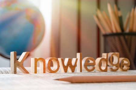Palabra de conocimiento en un libro y fondo estacionario de la escuela, concepto de educación y conocimiento Foto de archivo