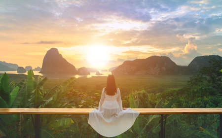 Woman with the white dress sit and see the mountain in early morning  at Samet Nangshe viewpoint in Andaman sea on morning cloudy sky, 版權商用圖片