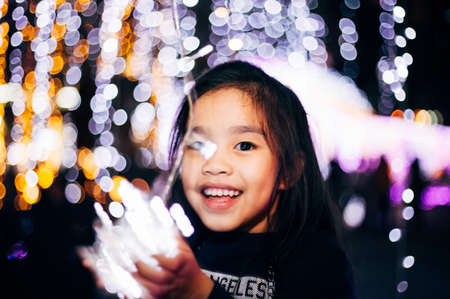 Happy children Holding a light on a New Years Eve.Street Night Scene with Christmas Lights. Christmas evening Concept 版權商用圖片