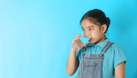 Little girl drinking water on blue background
