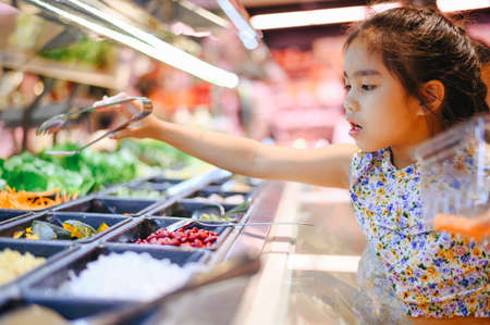 Little girl buying organic vegetables for Salad, Healthy salad bar in supermarket