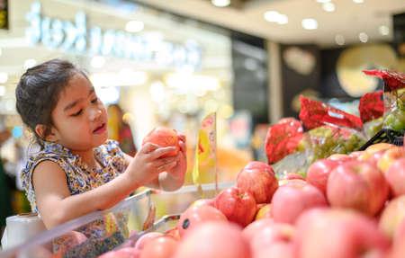 asian Little girl choosing a apple in a food store or a supermarket 版權商用圖片