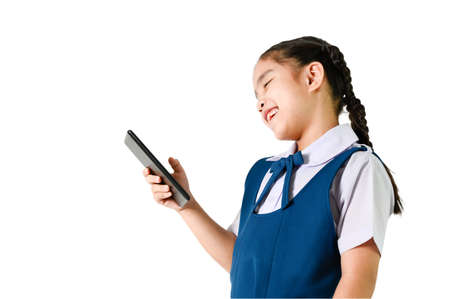 portrait of smiling, little girl in school uniform  touch the screen a digital device (pad, mobile, note) isolated white 版權商用圖片