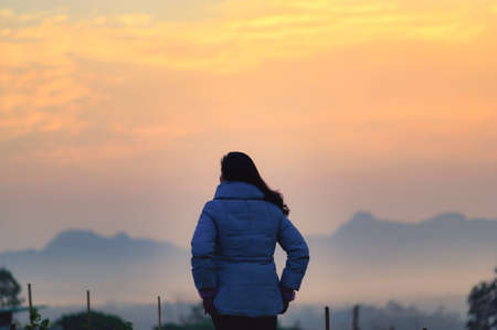 A young woman is looking at the Sun rise over the mountain