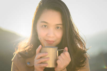 asia women tourist hold in hands mug of hot drink,  enjoy sun flare mountain , happy traveler drink cup of tea on nature